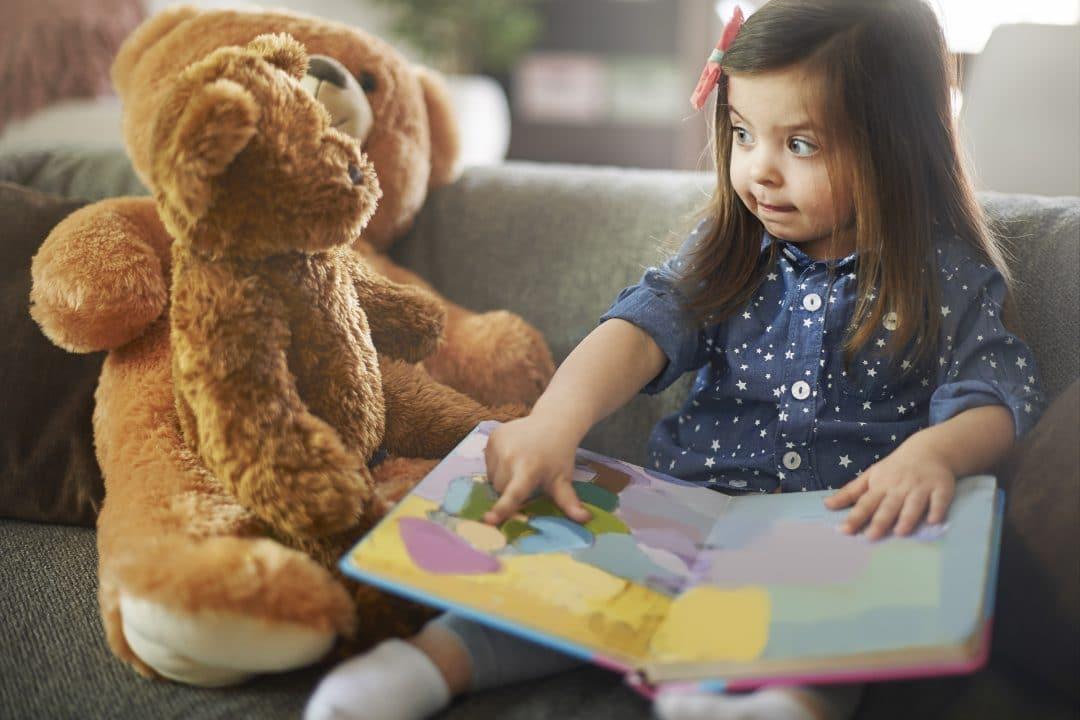 Storytelling. Niño contanto una historia a su oso