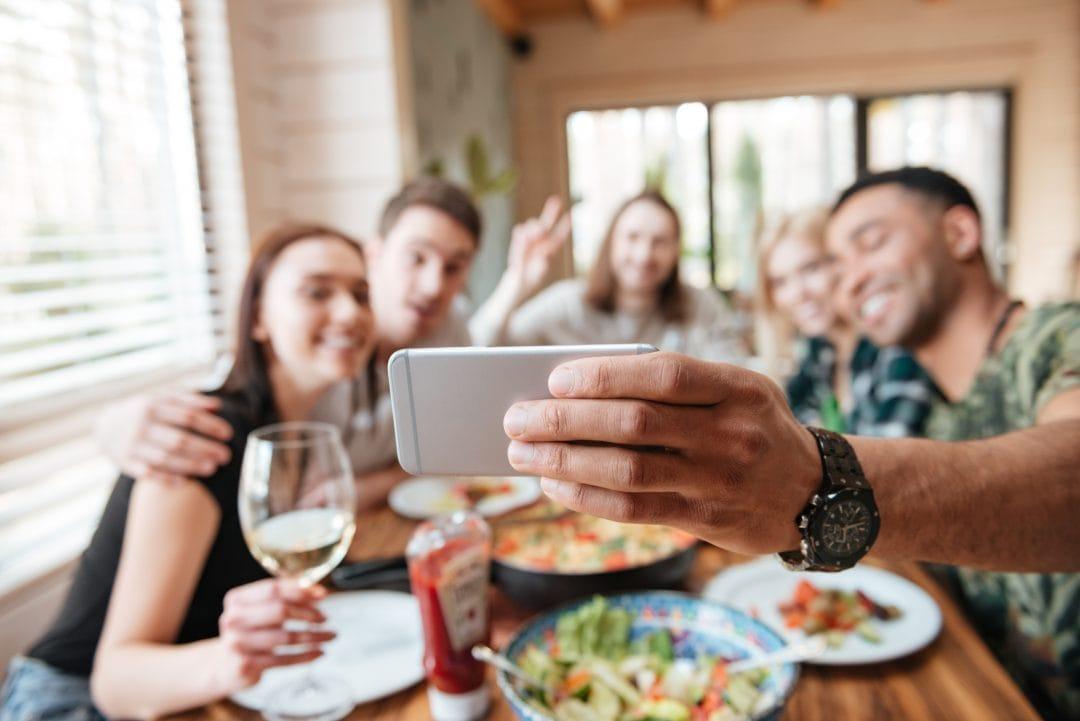 Grupo de amigos haciendo selfie en restaurante para redes sociales