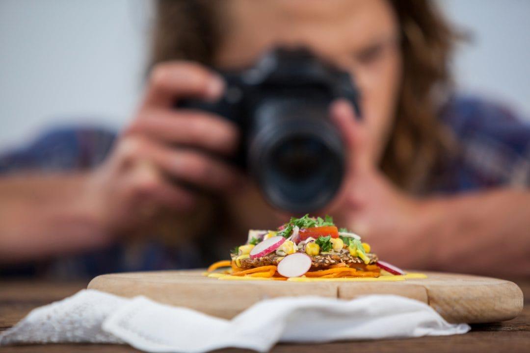 Hombre haciendo fotografía de estudio de un plato