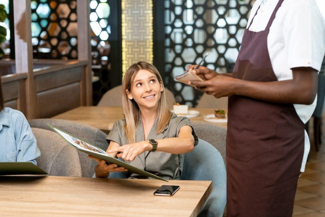 Camarero contestando una pregunta de la clienta