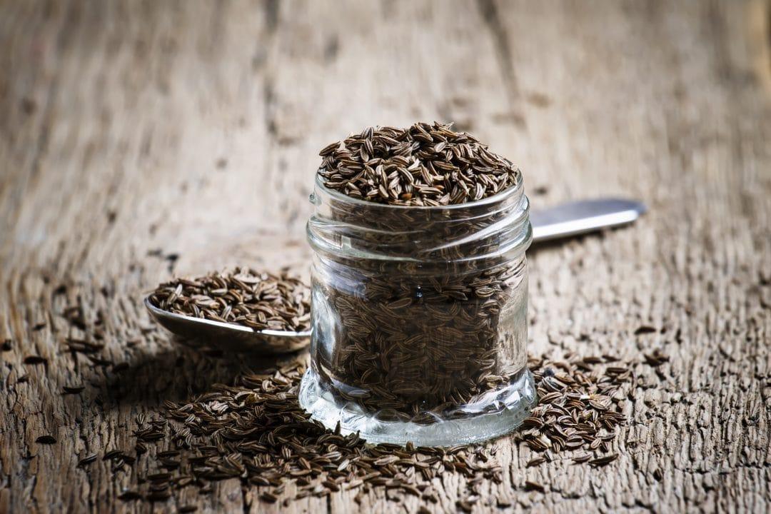 Tarro de cristal y cuchara con semillas de alcaravea