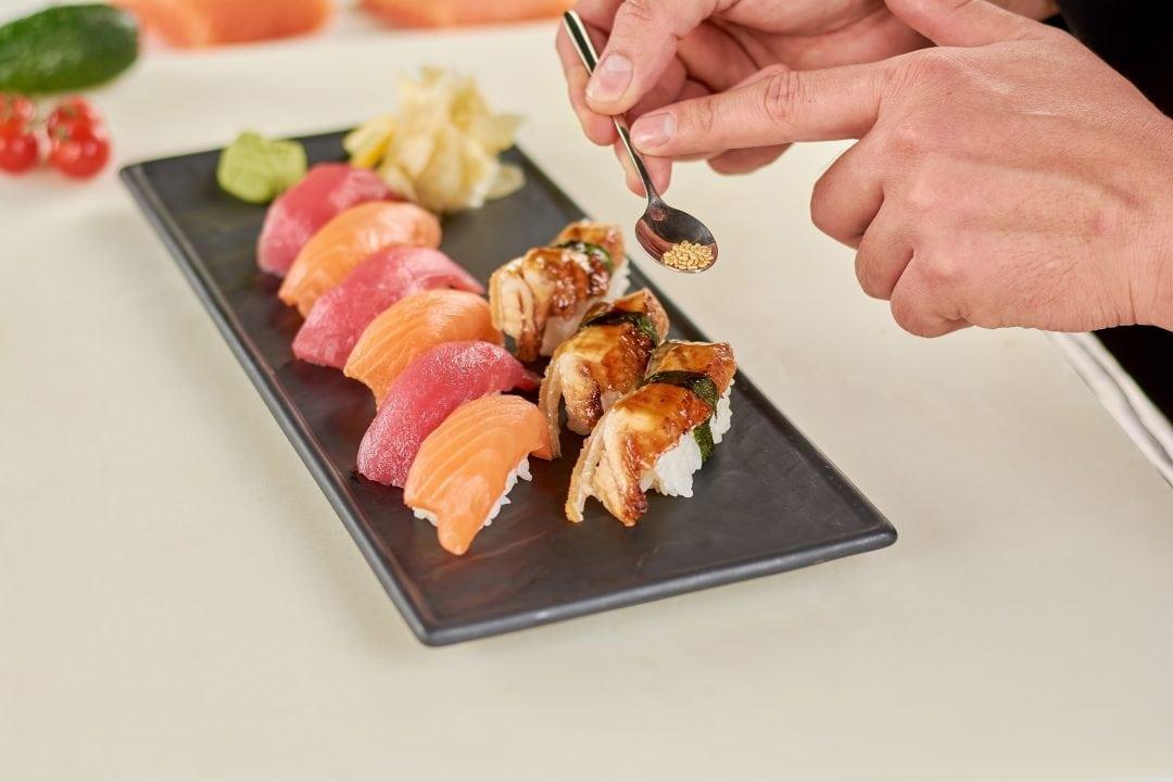Chef añadiendo sésamo al sushi