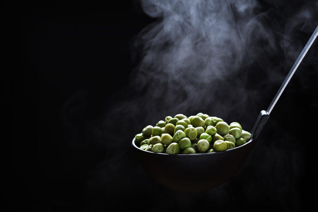 Cuchara con guisantes humeando, fotografía gastronómica