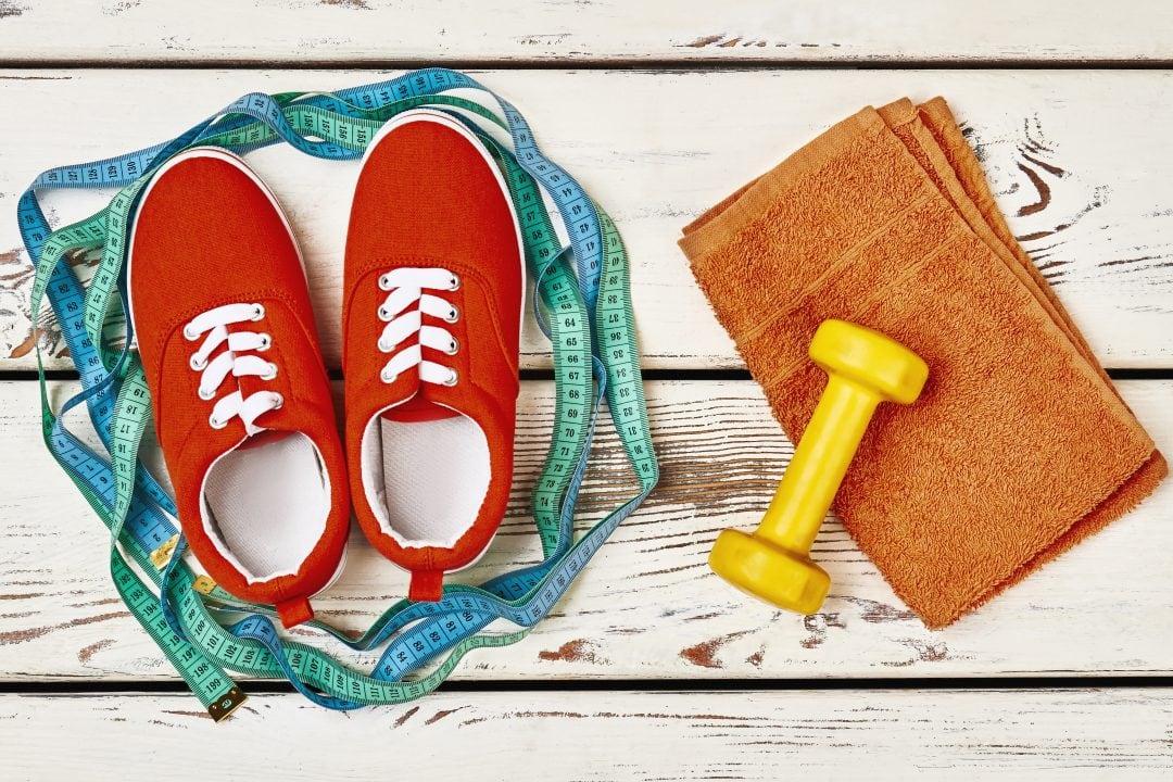 equipo puesta en forma, zapatillas, metro, pesa y toalla