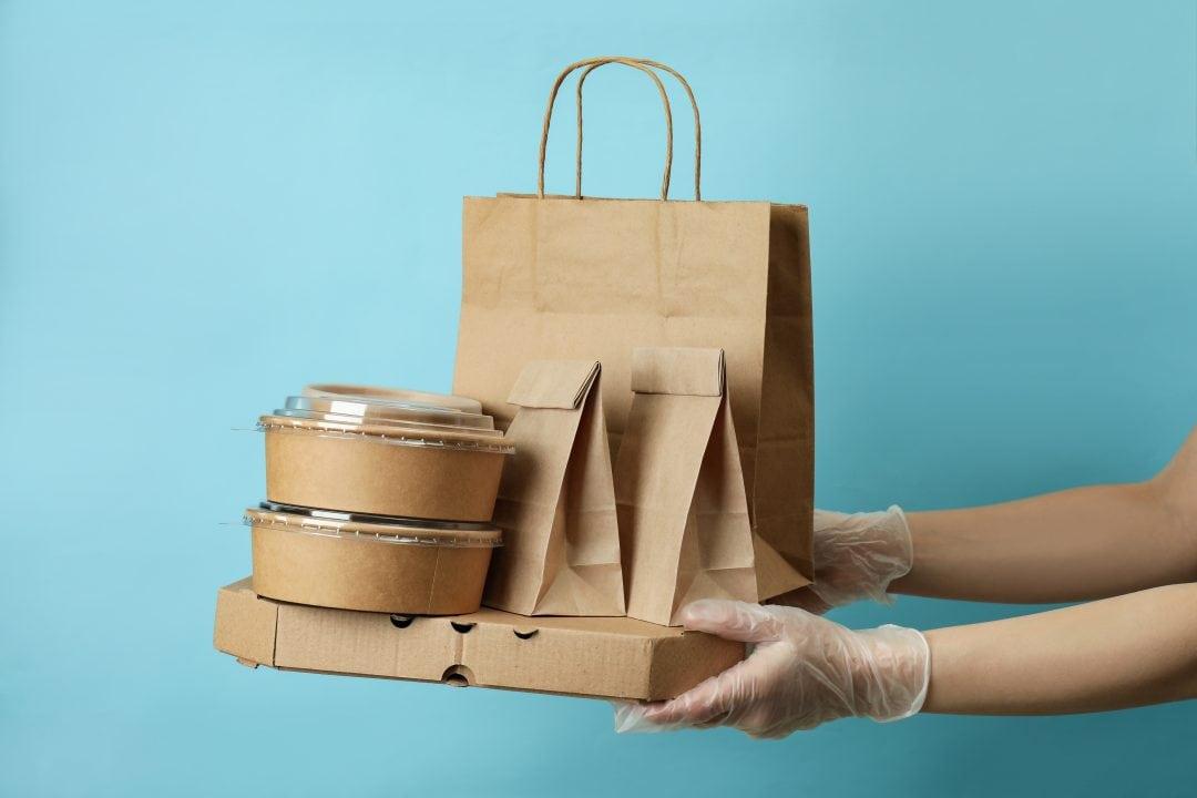 Manos con guantes entregando envases delivery seguro