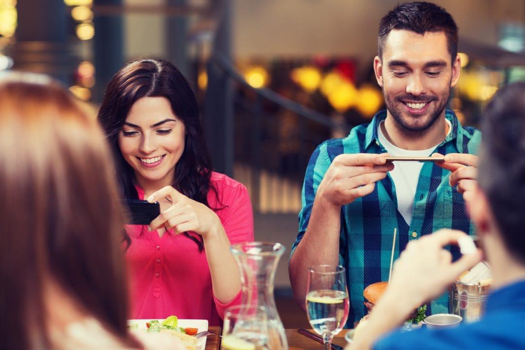 Clientes foddie fotografiando su comida en restaurante
