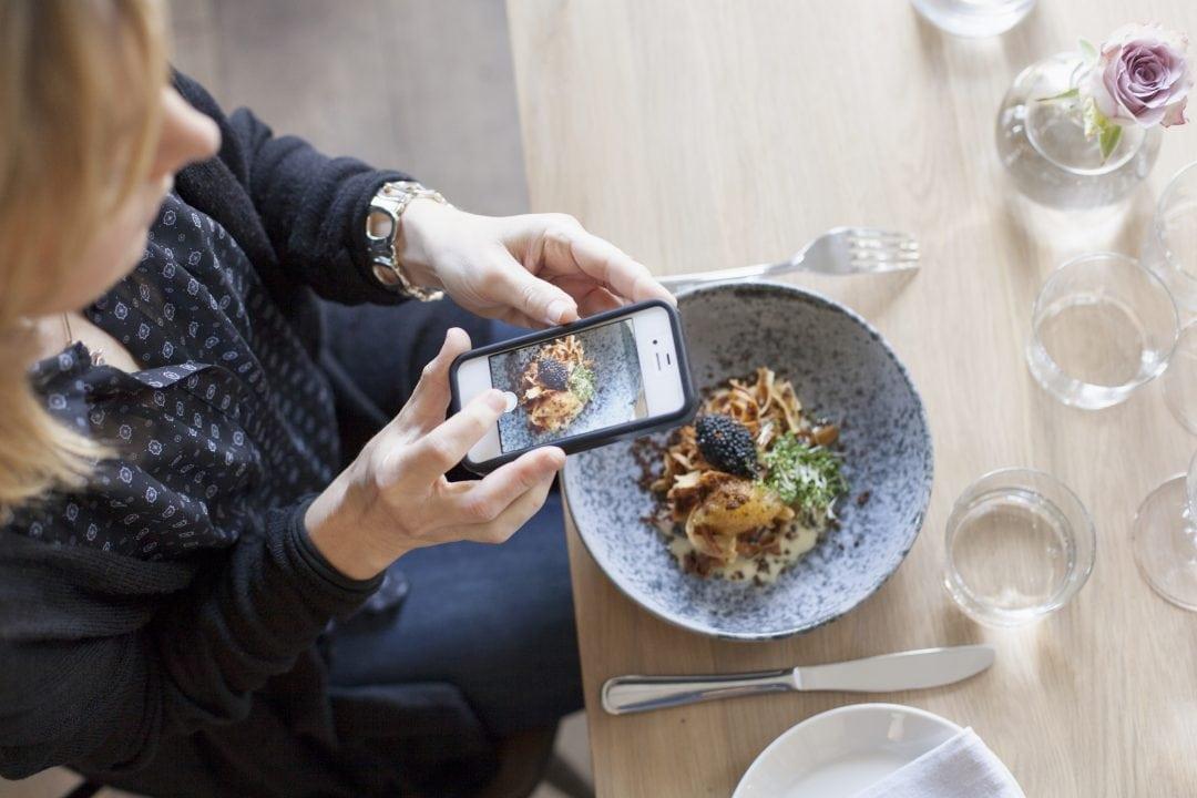 Foodie fotografiando su comida en el restaurante